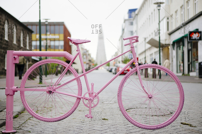 Pink painted bicycle on a street in Reykjavik Iceland