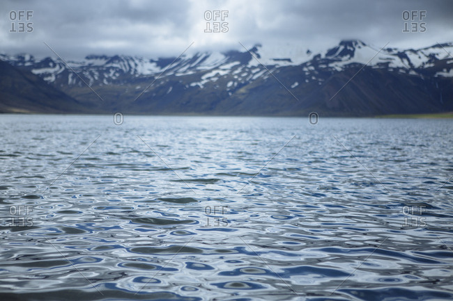 Water with snow capped mountains in background