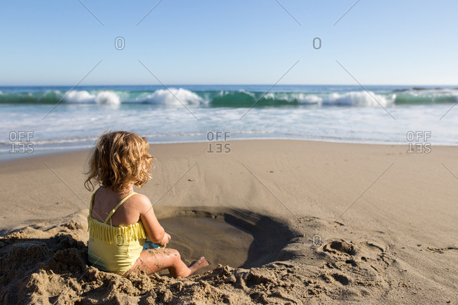 Young girl playing in a sandy hole at the beach