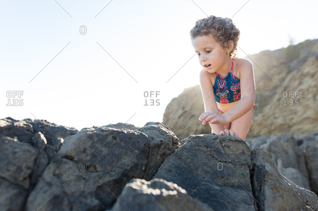 Young girl climbing on the rocks at the beach