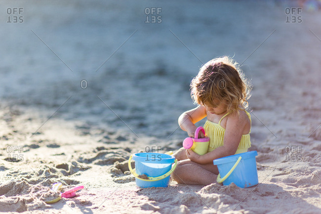A young girl playing with her buckets on the sand