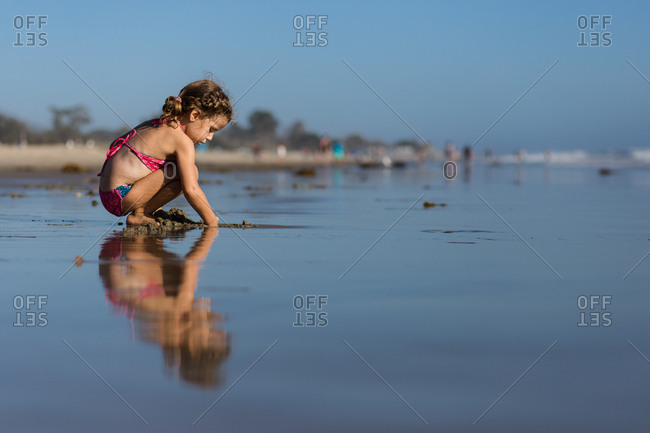Girl digging a hole in the sand
