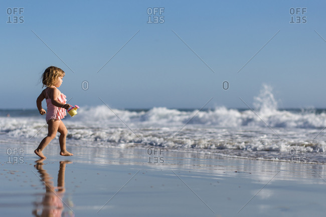 Young girl running towards the waves