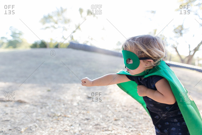 Child dressed as a superhero pretending to fly
