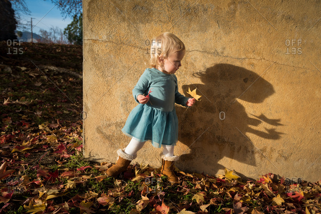 Toddler girl looking at shadow on wall