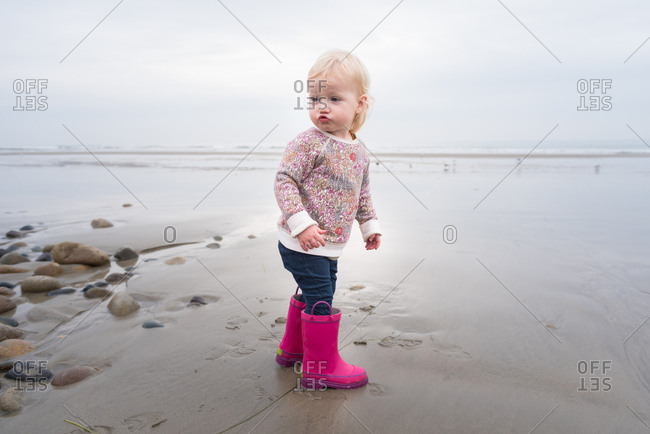 Toddler girl in pink boots on beach