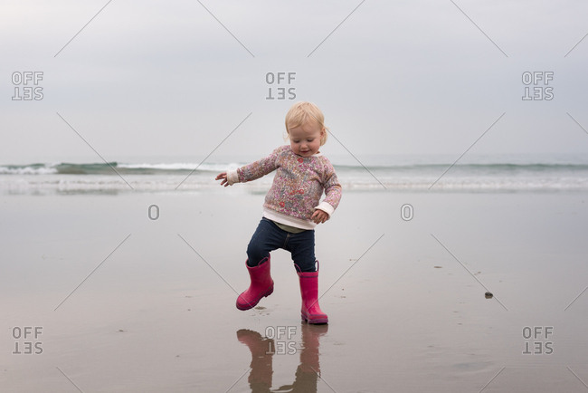 Toddler girl in pink boots walking on beach
