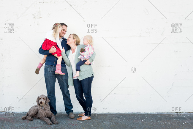Portrait of family of four with their dog