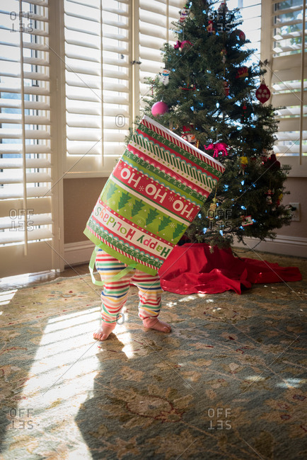 Baby in striped pajamas playing in Christmas bag