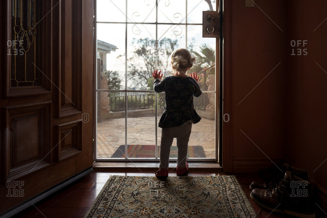 Back view of toddler girl looking out screen door