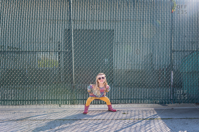 Playful young girl in sunglasses strikes a pose against chain link fence
