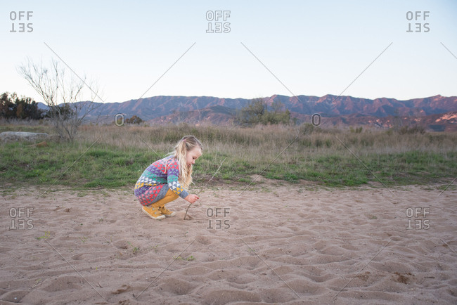 Young girl playing with stick in sand at dusk