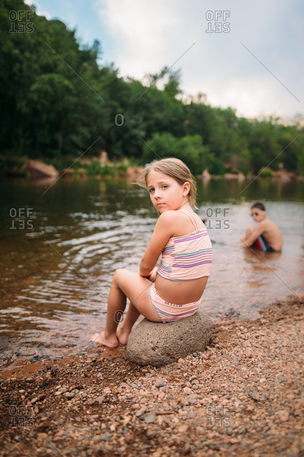 Kids sitting at a river's edge