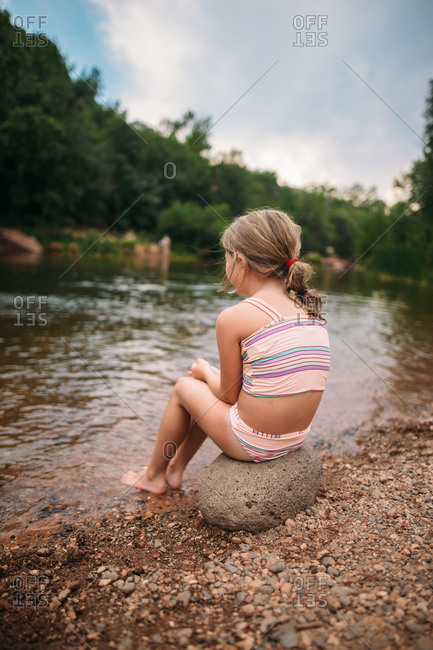 Girl on boulder by river's edge