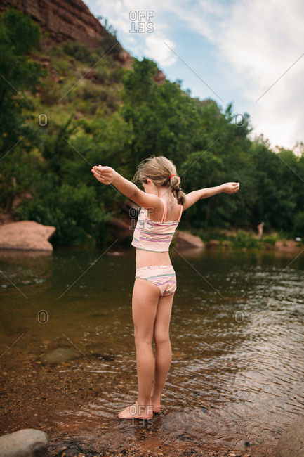 Girl with arms raised in river