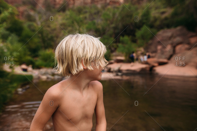 Blonde boy by river looking away