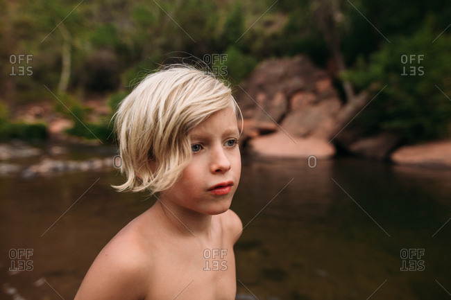 A blonde boy standing at river