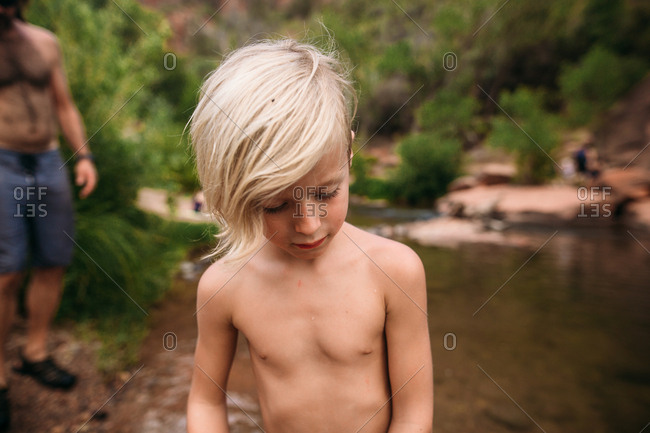 Blonde boy by a river looking down