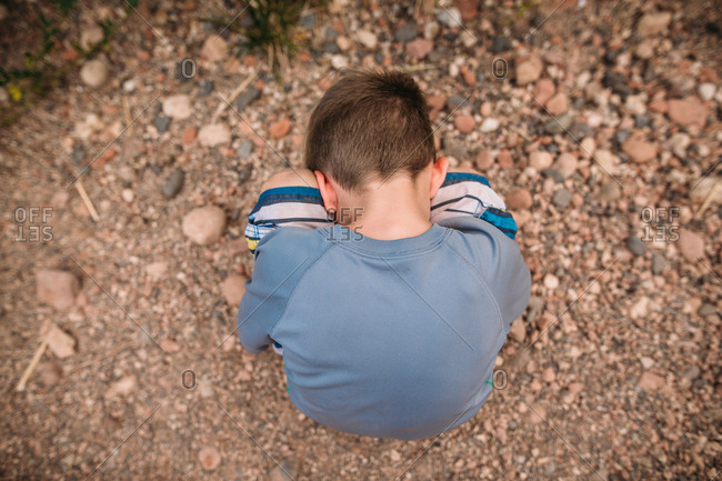 Boy with head in knees outside