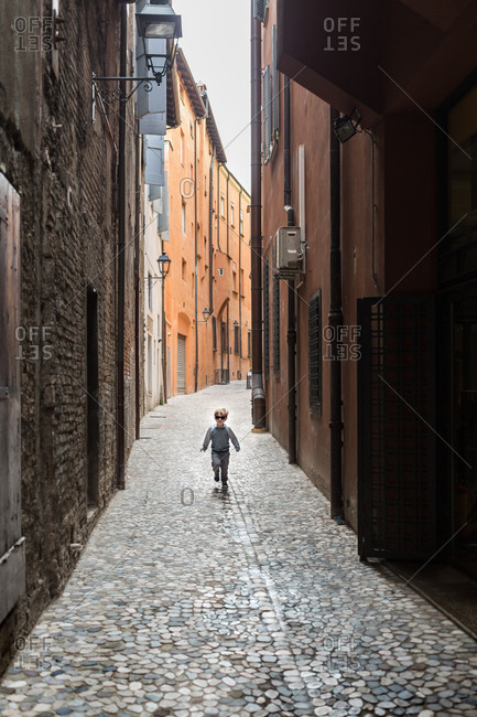 Boy walking cobblestone alley