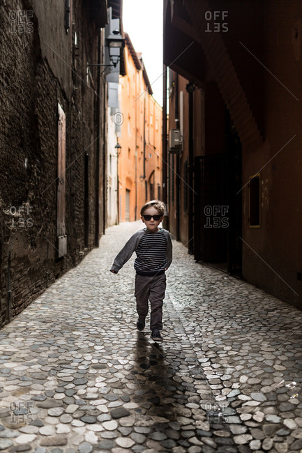 Boy walking in cobblestone alley