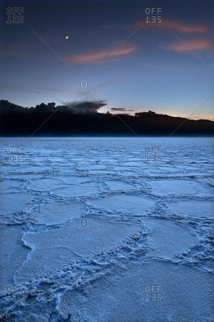 Salt flats with moon in sky