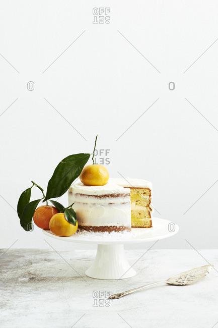 Vanilla citrus curd layer cake decorated with whole mandarin oranges.