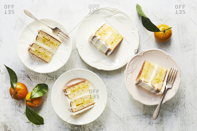 Slices of vanilla citrus curd layer cake decorated with whole mandarin oranges.