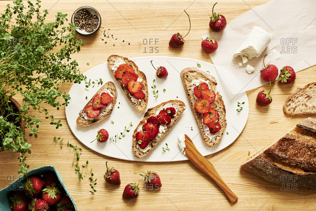 Overhead view of table set with strawberry, goat cheese and fresh herb tartines.