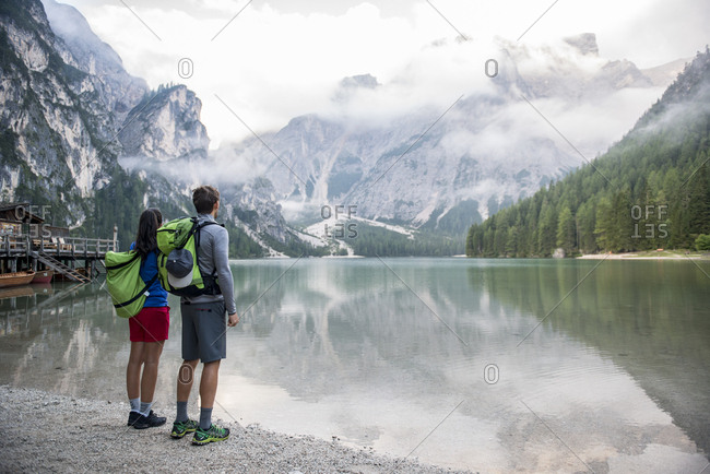 Latin woman and Caucasian man  looking at Braies lake with the Dolomites mountains in the background