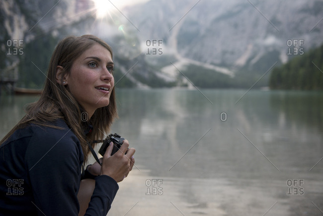 Caucasian woman taking photo of Braies lake with Dolomites mountain in the background