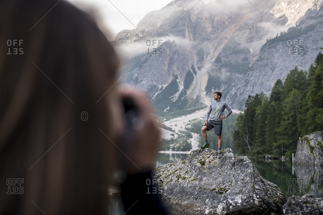 Caucasian woman taking photo of a friend at Braies lake with Dolomites mountain in the background