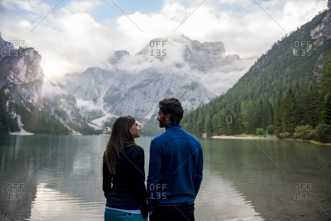 Caucasian woman and man looking at each other at Braies lake