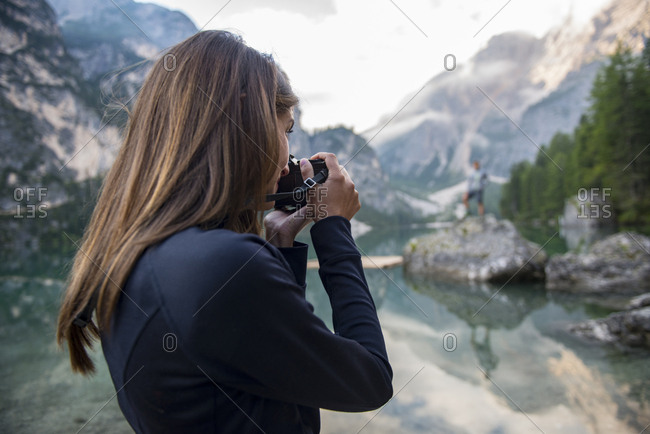Caucasian woman taking photo of friend at Braies lake with Dolomites mountain in the background