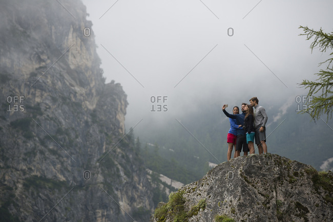 group of friends taking a selfie on a rock at Braies lake with Dolomites mountain in the background