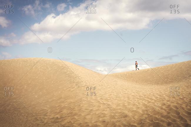 Tourist walking on sand dune