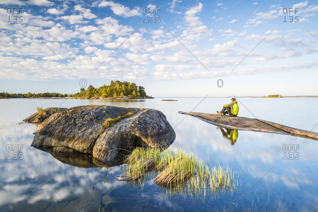 Man sitting on rock by lake on sunny day