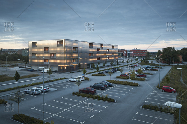 Modern residential building and parking lot at dusk