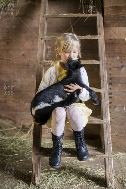 Girl sitting on ladder with goat