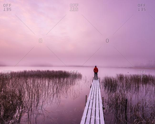 Man on jetty at sunrise