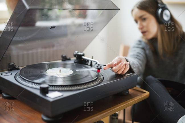 Woman with headphones listening to records