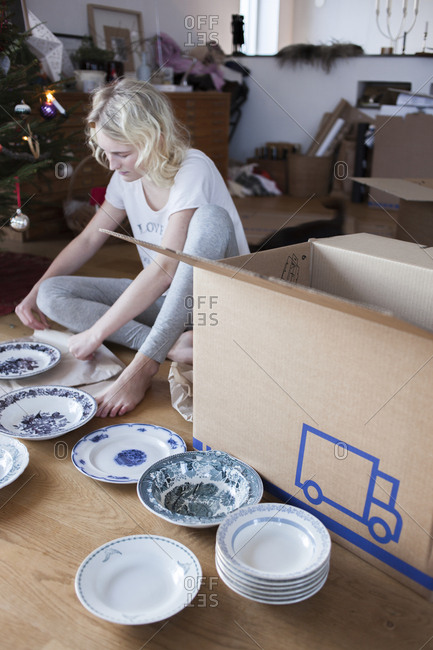 Teenage girl packing plates into moving box