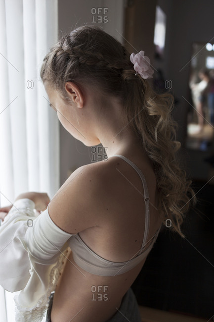 Girl getting dressed in domestic room