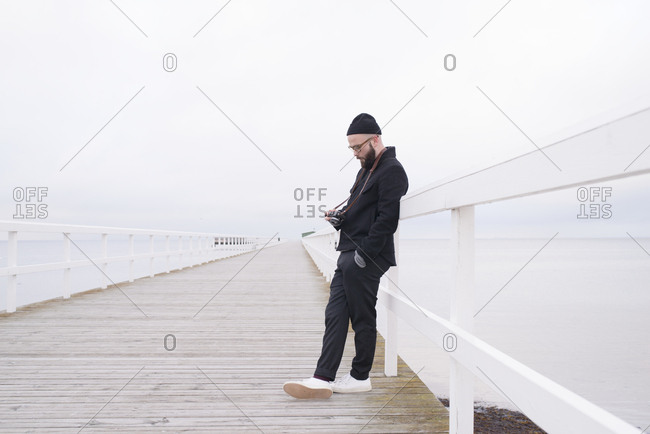 Man standing on pier with camera