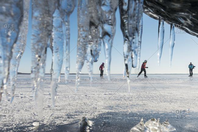 Three people ice-skating