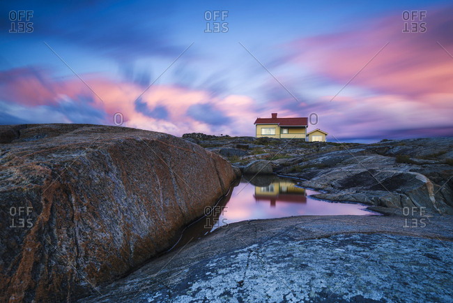House on rocky coast at twilight