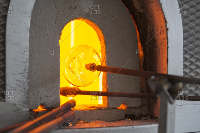 Glassblowers heating glass in kiln