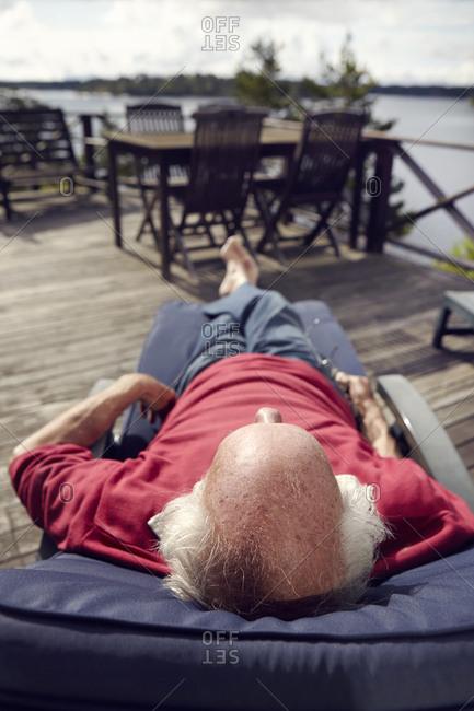 Senior man lying on sun chair