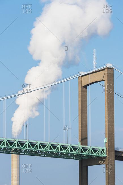 Bridge with smoking chimney on background