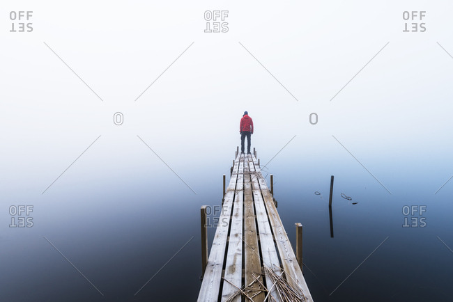 Man standing at the end of wooden pier